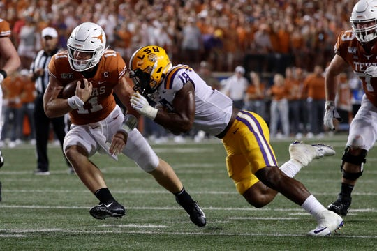Texas quarterback Sam Ehlinger tries to break a tackle by LSU linebacker K'Lavon Chaisson (18) during the second half of an NCAA college football game Saturday, Sept. 7, 2019, in Austin, Texas. (AP Photo/Eric Gay)