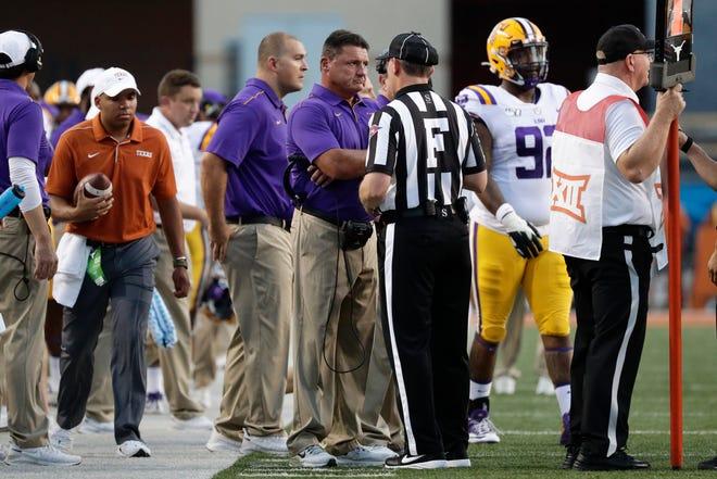 LSU head coach Ed Orgeron, center, questions a call during the first half of an NCAA college football game against Texas, Saturday, Sept. 7, 2019, in Austin, Texas. (AP Photo/Eric Gay)