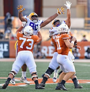 LSU defensive linemen Rashard Lawrence (90) and Breiden Fehoko (91) are held back by Texas offensive linemen Parker Braun (73) and Zach Shackelford (56) as quarterback Sam Ehlinger (11) drops back to pass during an NCAA college football game Saturday, Sept. 7, 2019, in Austin, Texas. (Hilary Scheinuk/The Advocate via AP)