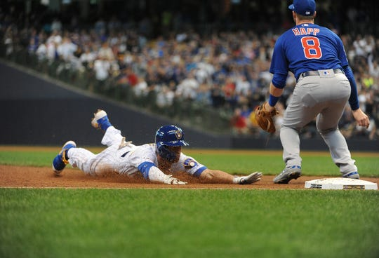 Cory Spangenberg of the Brewers dives into third base for a triple as Cubs third baseman Ian Happ awaits the throw in the sixth inning.