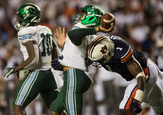 Tulane quarterback Justin McMillan (12) is hit by Auburn defensive lineman Big Kat Bryant (1) as he throws the ball at Jordan-Hare Stadium in Auburn, Ala., on Saturday, Sept. 7, 2019. Auburn defeated Tulane 24-6.