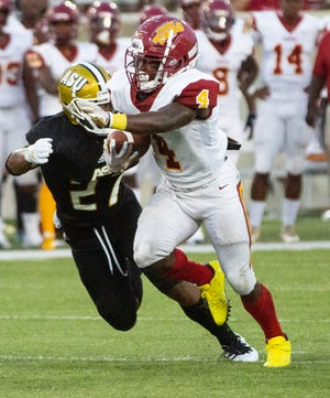 Tuskegee's Taurean Taylor (4) runs the ball as ASU's Aaron Pope (27) attempts a tackle.