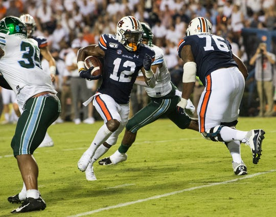 Auburn wide receiver Eli Stove (12) finds a hole as he runs in for a touchdown at Jordan-Hare Stadium in Auburn, Ala., on Saturday, Sept. 7, 2019.