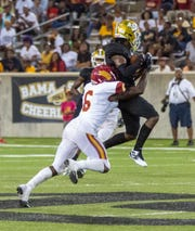 Tuskegee's Brandon Roberts (6) tries to bring ASU's Jeremiah Hixon (1) down during a third quarter catch.