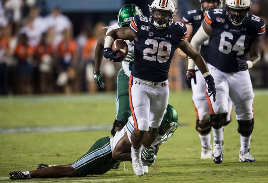 Auburn running back JaTarvious Whitlow (28) is tripped up as he runs the ball at Jordan-Hare Stadium in Auburn, Ala., on Saturday, Sept. 7, 2019. Auburn defeated Tulane 24-6.
