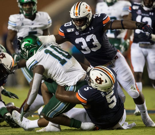 Tulane running back Darius Bradwell (10) is pulled down by Auburn defensive lineman Derrick Brown (5) with assistance by linebacker K.J. Britt (33) at Jordan-Hare Stadium in Auburn, Ala., on Saturday, Sept. 7, 2019. Auburn leads Tulane 14-6 at halftime.
