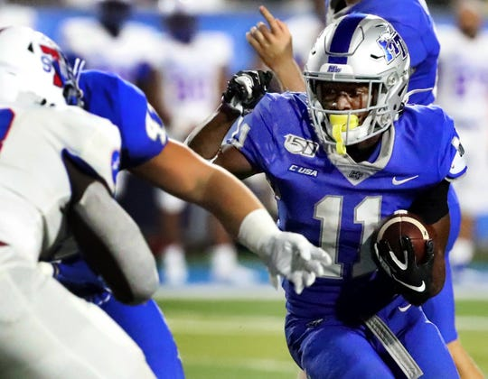 MTSU running back Brad Anderson (11) runs the ball as TSU linebacker Terry Straughter (18) moves in for the tackle during their game Sept. 7.