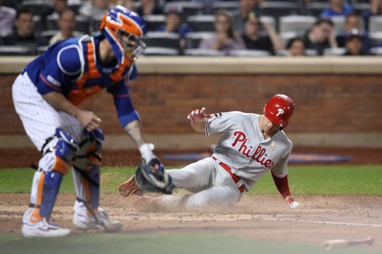 Philadelphia Phillies' Scott Kingery scores past New York Mets catcher Tomas Nido on a hits an RBI single by Cesar Hernandez during the fourth inning of a game, Saturday, Sept. 7, 2019, in New York.