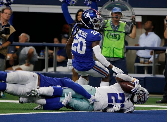 New York Giants' Alec Ogletree, left, and Janoris Jenkins (20) are unable to stop Dallas Cowboys running back Ezekiel Elliott (21) from reaching the end zone for a touchdown in the second half of a NFL football game in Arlington, Texas, Sunday, Sept. 8, 2019. (AP Photo/Michael Ainsworth)
