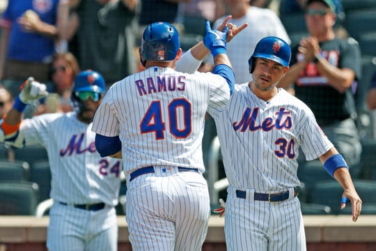New York Mets' Michael Conforto, right, greets Wilson Ramos (40) after scoring on Ramos's first-inning wo-run home run in a baseball game against the Philadelphia Phillies, Sunday, Sept. 8, 2019, in New York. On-deck batter Robinson Cano (24), joins in.  (AP Photo/Kathy Willens)