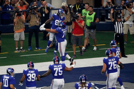 New York Giants' Evan Engram (88) and Will Hernandez (71) celebrate a touchdown catch by Engram as others look on in the first half of a NFL football game against the Dallas Cowboys in Arlington, Texas, Sunday, Sept. 8, 2019. (AP Photo/Roger Steinman)