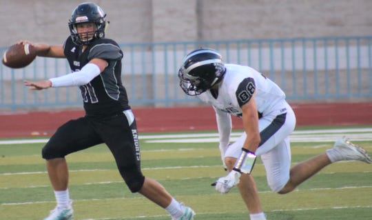 Oñate quarterback Aiden Rosser rolls out of the pocket while being pursued by Volcano Vista's Cody Moon on Saturday night at the Field of Dreams.