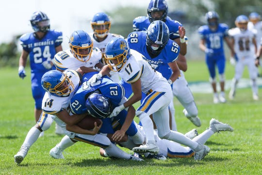 Bloomfield's Emilio Candelaria (#14), Kenyon Mosley (#30) and Michael Bahannon (#17) sack St. Michaels quarterback Lucas Coriz in the back field in the second quarter on Saturday in Santa Fe.