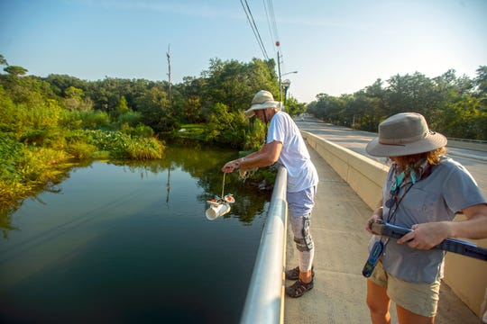 Barbara Albrecht with the Florida Bream Fishermen's Association, a citizen water quality monitoring and watchdog group established in the late 1960s, and University of West Florida student volunteer Jessica Baker, right, take water samples off of 12th Avenue on Sept. 8.