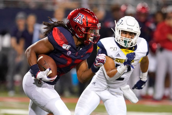 Arizona running back Gary Brightwell (23) runs away from Northern Arizona defensive back Anthony Sweeney in the second half during an NCAA college football game, Saturday, Sept. 7, 2019, in Tucson, Ariz. (AP Photo/Rick Scuteri)