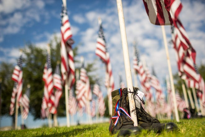 Boots sit at the base of a flag at the Healing Fields on Saturday, Sept. 7, 2019 at Tempe Beach Park. The flags pay tribute to the victims of the 9/11 attacks.