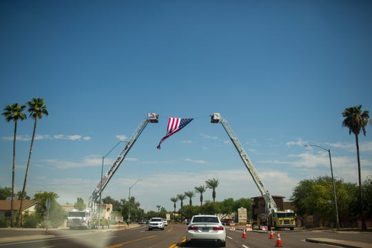 A flag is held up by two fire ladders outside of the memorial service for Fire Engineer Austin Peck Saturday, Sept. 7, 2019, at Dubliner Irish Pub in Phoenix. Peck died of cancer Aug. 31, 2019.