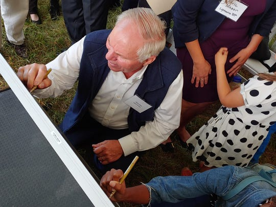 Glenn Dice signs a solar panel Friday, Sept. 6, 2019. He is leasing part of his land to Lightsource BP and Penn State.