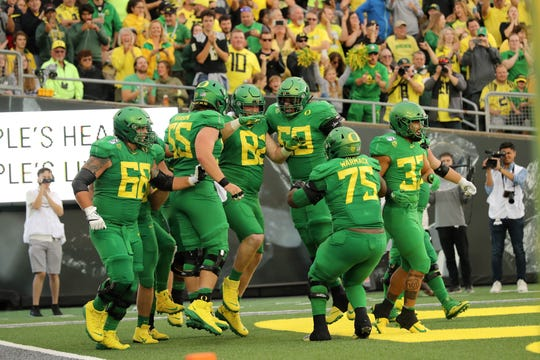Oregon offensive lineman Brady Aiello (82) celebrates with teammates after scoring a touchdown against Nevada on Saturday.