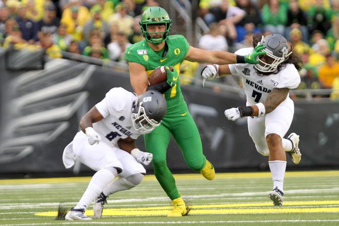Oregon tight end  Jacob Breeland picks up yardage against Nevada linebacker Gabriel Sewell (7) and safety Emany Johnson during Saturday's game.