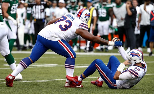 Dion Dawkins, left, of the Buffalo Bills helps Josh Allen to his feet after a sack against the New York Jets during a game at MetLife Stadium on September 8, 2019.
