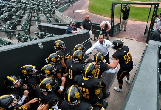 McQuaid head coach Bobby Bates, top, fires up his players before leading them onto the field against Aquinas before the season opener played at Frontier Field, Saturday, Sept. 7, 2019.