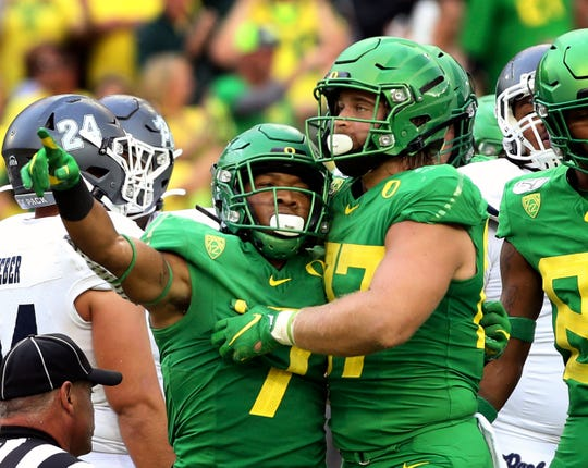 Oregon's CJ Verdell, left, and Ryan Bay, right, celebrate a touchdown during the second quarter of an NCAA college football game against Nevada, Sept. 7, 2019, in Eugene, Ore.