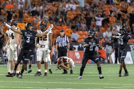 Hawaii defensive backs Kalen Hicks (3), Khoury Bethley (5) and Cortez Davis (18) celebrate after Oregon State place kicker Jordan Choukair (46) misses a game tying field goal late in the second half of an NCAA college football game, Sept. 7, 2019, in Honolulu. Hawaii beat Oregon State 31-28.