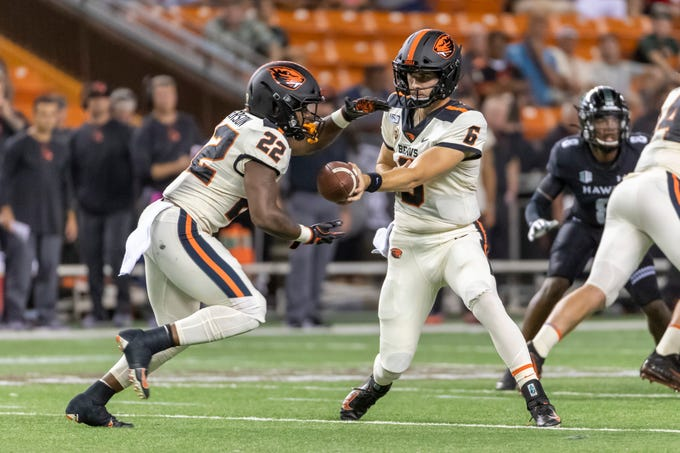 Oregon State quarterback Jake Luton (6) hands off the football to his running back Jermar Jefferson (22) during the first half of an NCAA college football game, Sept. 7, 2019, in Honolulu.
