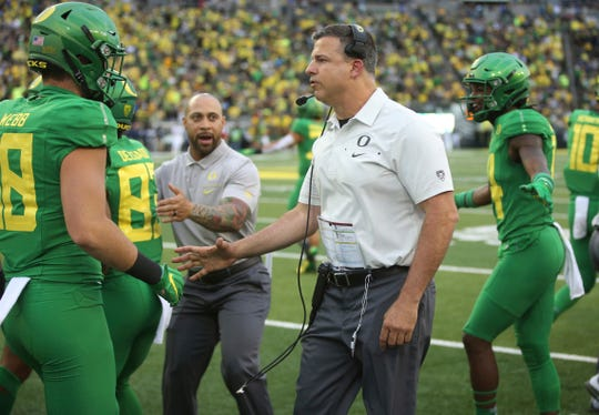 Oregon head coach Mario Cristobal, center, celebrates a touchdown in the fourth quarter against Nevada in an NCAA college football game, Sept. 7, 2019, in Eugene, Ore.