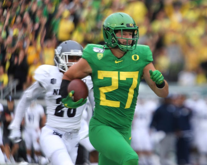Oregon's Jacob Breeland (27) outruns Nevada's Austin Arnold, left, on his way to a touchdown during the first quarter of a NCAA college football game Sept. 7, 2019, in Eugene, Ore.