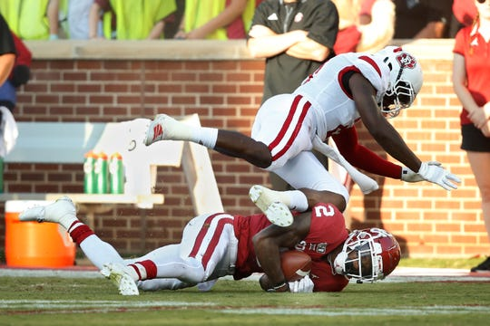 South Dakota defensive back Phillip Powell tumbles over Oklahoma wide receiver CeeDee Lamb (2) after Lamb catches a pass in the first quarter of an NCAA college football game Saturday, Sept. 7, 2019, in Norman, Okla. (AP Photo/Sue Ogrocki)