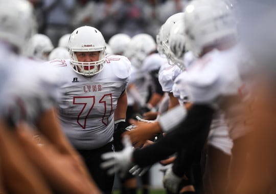 Brandon Valley lineman Zach Bennett (71) runs through a tunnel of Brandon Valley players before the Bob Burns Dakota Bowl at Howard Wood Field on Saturday, Sept. 7, 2019.
