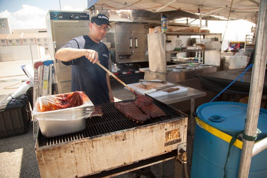 Barbecue vendor from Austin's Texas Lightning BBQ coats ribs in barbecue sauce during the CasaBlanca Rib Fest on Sept. 7, 2019.