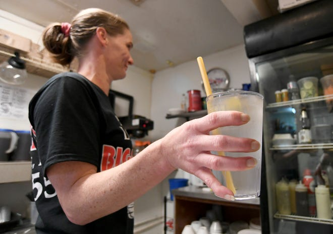 Jill Wagner, server at Pappa Louie's Italian Restaurant, prepares a glass of water using a pasta straw instead of plastic, for a customer on Sunday, Aug. 25, 2019, in Port St. Lucie. The restaurant has switched from plastic straws to pasta straws to help cut the volume of single-use plastic straws littering Florida beaches and waterways.