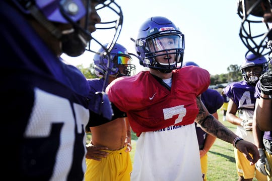 Cal Lutheran University quarterback Cesar De Leon huddles his offense at practice.