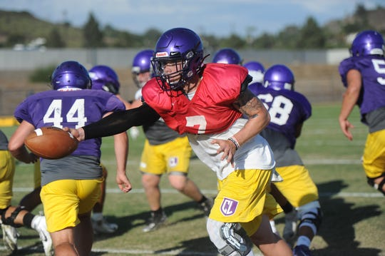Cal Lutheran University quarterback Cesar De Leon hands off the ball at practice.