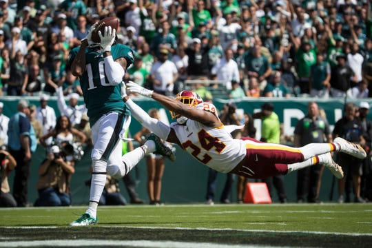 Eagles' DeSean Jackson (10) brings in a deep pass in front of a diving Josh Norman (24) to score last Sunday at Lincoln Financial Field.