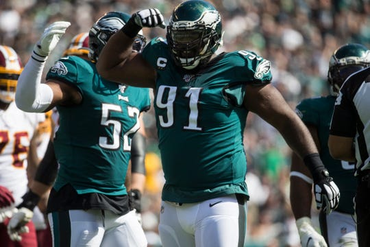 Eagles' Fletcher Cox (91) shows off his muscles after making a tackle Sunday at Lincoln Financial Field.