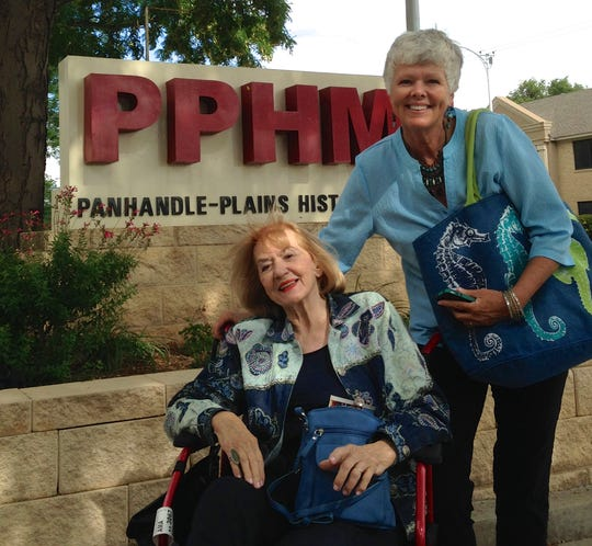 """More than a care-giver, Wendee Rogers holds some of Marybeth Weston's paraphernalia under her arm during Weston's 2014 visit to a tourism event in Canyon, Texas. Trained in linguistics, Rogers helped Weston with efforts to get her one-woman play, """"The Comanche with Blue Eyes,"""" back into print."""