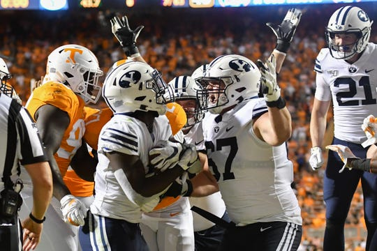 BYU Cougars running back Ty'Son Williams celebrates with teammates after scoring the winning touchdown.