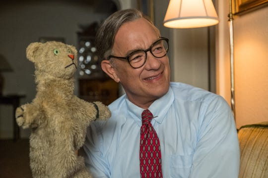 "Fred Rogers (Tom Hanks) breaks out Daniel Tiger for a new friend in ""A Beautiful Day in the Neighborhood."""