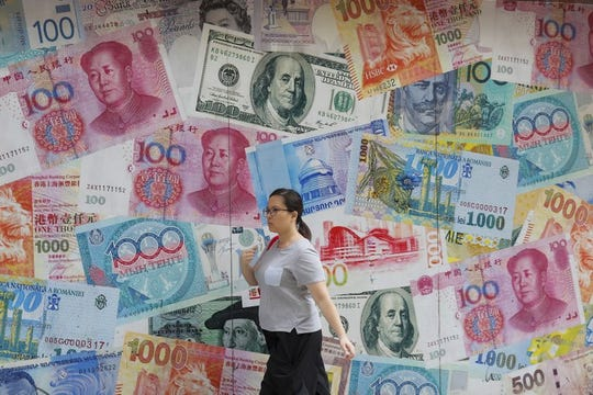 In this Aug. 6, 2019, file photo, a woman walks by a money exchange shop decorated with different countries currency banknotes at Central, a business district in Hong Kong. China's trade with the United States fell sharply in August as a tariff war that threatens global economic growth worsened.