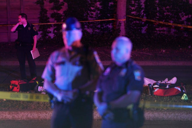 Police stand in front of a body at the scene of an officer involved shooting on East 77th Street in Richfield, Minn., Saturday night, Sept. 7, 2019.