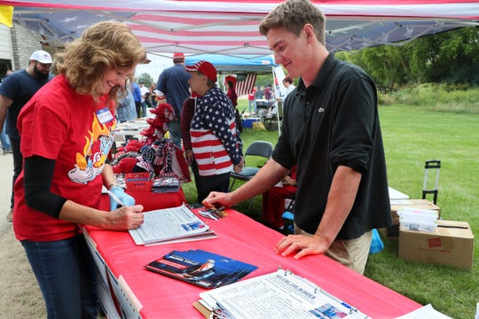 Redmond Tuttle, of Milwaukee, watches as he oversees people signing petitions urging congress to support the 2nd amendment and secure our borders at the annual Chicken Burn in Greenfield on Sept. 8, hosted by the Wisconsin Conservative Digest and promoted on social media by Walkaway Milwaukee. At left, is Edith Gamble of Franklin. Michael Sears/Milwaukee Journal Sentinel