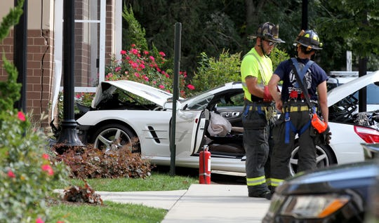 Firefighters stand by with a vehicle that crashed into the side of Hesse Hall at Monmouth University in West Long Branch Monday afternoon, September 9, 2019.  This vehicle had also backed into another parked car.