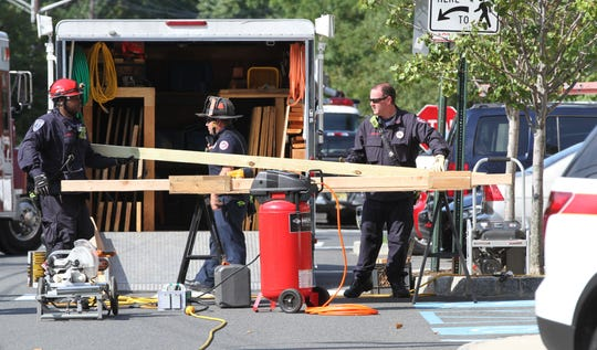Asbury Park Firefighters prepare to add braces to Hesse Hall at Monmouth University in West Long Branch Monday afternoon, September 9, 2019, after it was struck by a car that had also rear-ended another vehicle there.