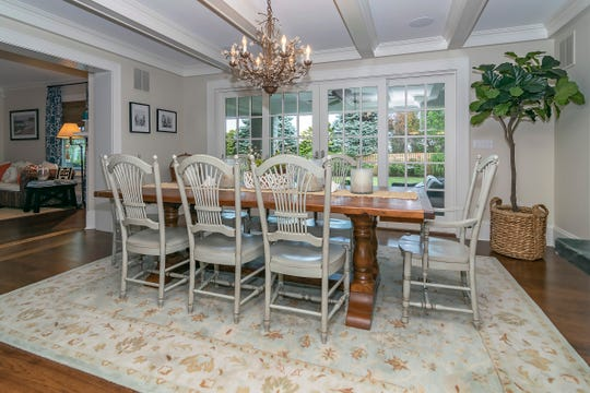The dining room features a set of French doors and beamed ceilings.