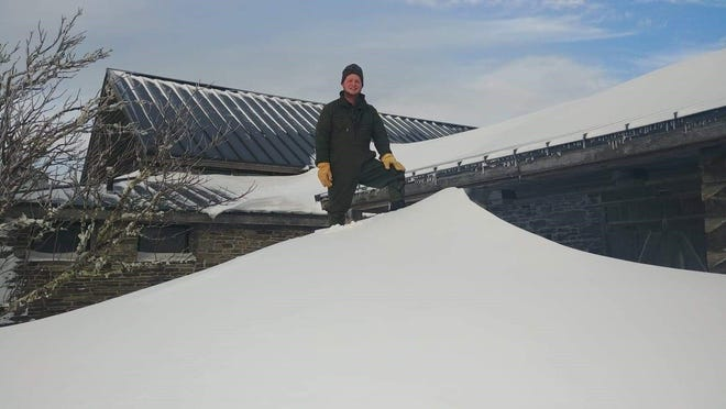 Not surprisingly, Mount Mitchell the highest point east of the Mississippi River at 6,684 feet, gets the most snowfall in the state of North Carolina. In this photo from Dec. 11, 2018, Mount Mitchell seasonal park technician Kevin Cox stands on top of a snow drift several feet high outside the park restaurant.