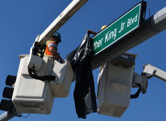 A Melbourne city worker installs a new Martin Luther King Jr. Boulevard road sign Monday morning at the intersection of Airport and Hibiscus boulevards.